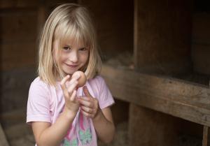Bauernhofurlaub Kind mit Hühner Ei